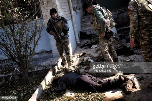 A member of the Iraqi forces stands over a body in Mosul on March 5 during an offensive to retake the western parts of the city from the jihadists...