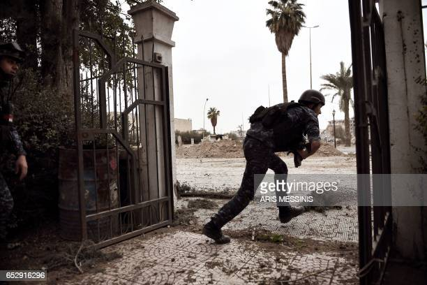 A member of the Iraqi forces takes cover from sniper fire in a western neighbourhood of Mosul on March 13 during an offensive to retake the city from...