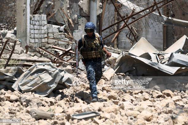TOPSHOT A member of the Iraqi forces walks amidst the rubble during their advance towards Mosul's Old City on June 18 during the ongoing offensive by...