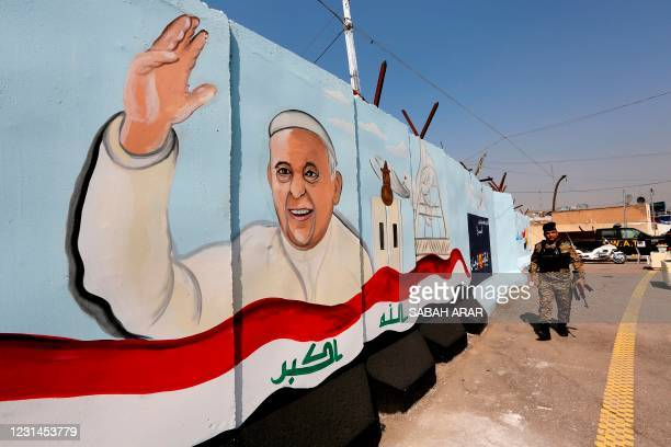 Member of the Iraqi forces walks past a mural depicting Pope Francis waving next to an Iraqi national flag drawn on a blast wall outside the Syriac...