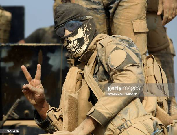 TOPSHOT A member of the Iraqi government forces flashes the sign for victory as they enter the village of alKhuwayn south of Mosul after recapturing...