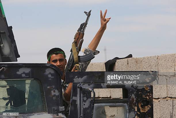 A member of the Iraqi government forces flashes the Vsign as he holds a position on the western outskirts of Tikrit on March 27 during a military...