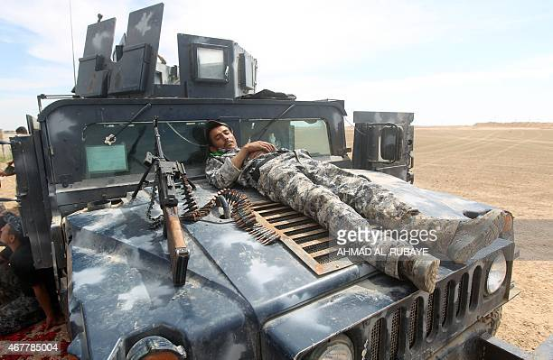 A member of the Iraqi government forces rests on his vehicle positioned on the western outskirts of Tikrit on March 27 during a military operation to...