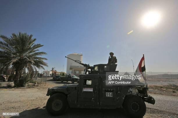 A member of the Iraqi government forces stands guard in a humvee turret while guarding the Bai Hassan oil field west of the multiethnic northern...