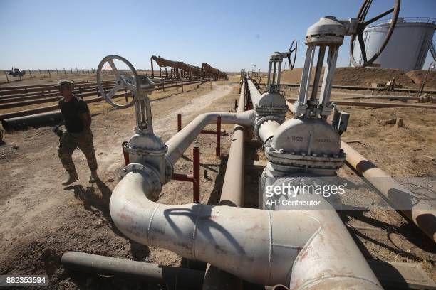 A member of the Iraqi government forces walks through the Bai Hassan oil field west of the multiethnic northern Iraqi city of Kirkuk on October 17...