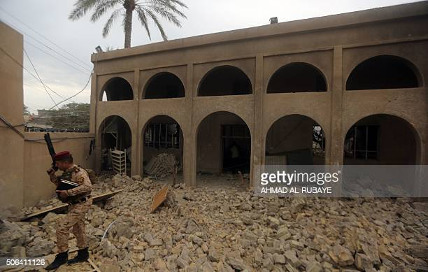 A member of the Iraqi security forces checks the damage at a Sunni mosque that was destroyed during violence earlier in the month in the town of...