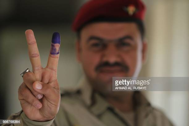 TOPSHOT A member of the Iraqi security forces flashes the 'v' sign for victory after voting at a polling station in the Iraqi capital Baghdad to vote...