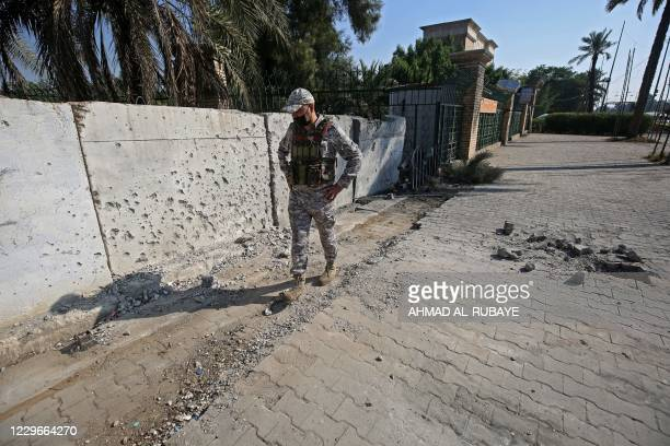 Member of the Iraqi security forces inspects the damage outside the Zawraa park in the capital Baghdad on November 18 after volley of rockets slammed...