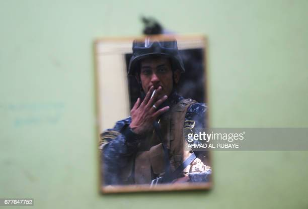 Member of the Iraqi security forces is reflected in a mirror while holding a position on the front line in Mosul's Old City on May 3 during an...