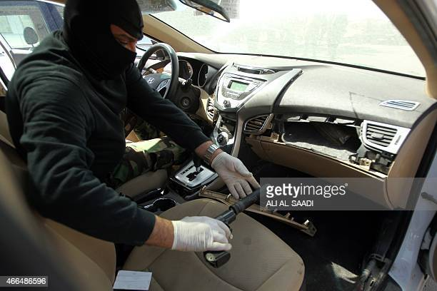 A member of the Iraqi security forces pulls out a gun on March 16 2015 from a hidden compartment inside a car seized in Baghdad along with 31...
