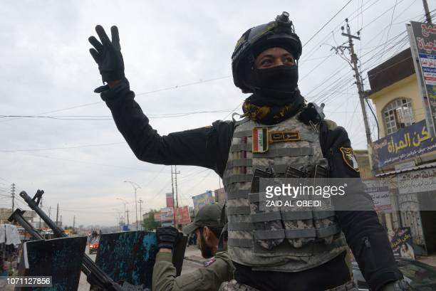 A member of the Iraqi security forces salutes onlookers as he parades in the streets of the Iraqi city of Mosul during celebrations marking the first...
