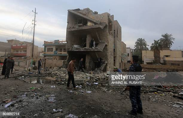 A member of the Iraqi security forces takes photos of the damage near the alJawaher mall in eastern Baghdad the day after a bomb attack on January 12...