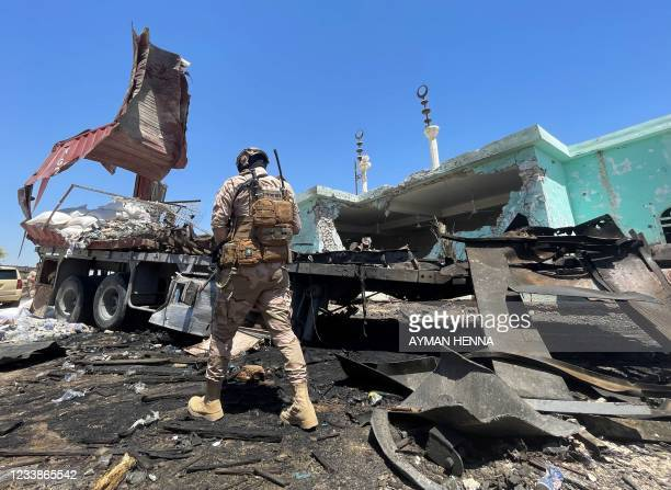 Member of the Iraqi security forces walks past a destroyed vehicle that was carrying rockets amdist sacks of flour, in the district of al-Baghdadi in...