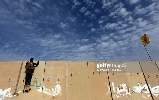 A member of the Iraqi security forces watches clashes from over a blast wall outside the western entrance of the city of Tikrit on March 28 2015...