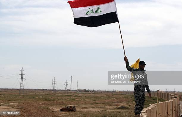 A member of the Iraqi security forces waves the national flag as he stands atop a blast wall outside the western entrance of the city of Tikrit on...