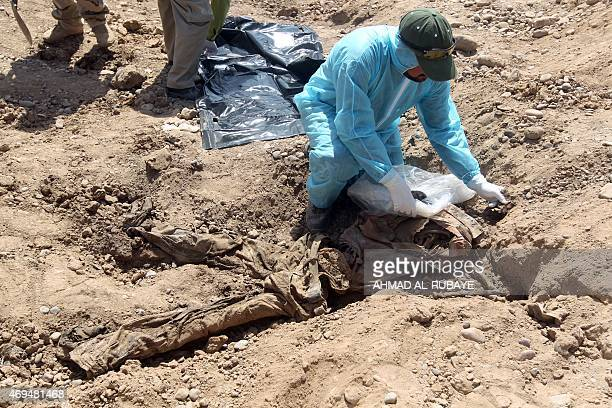Member of the Iraqi security forces wearing protective clothes inspects a mass grave containing the remains of dozens of people believed to have been...