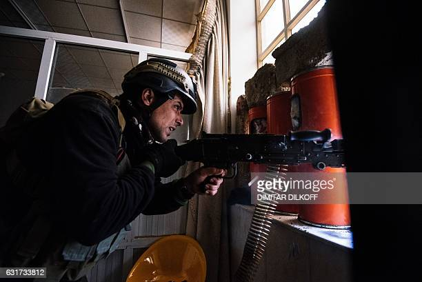 Member of the Iraqi special forces' Counter-Terrorism Service fires his machine gun as he holds a position inside Mosul's university on January 15...