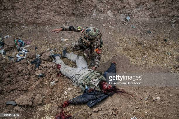 A member of the Iraqi Special Operations Forces inspects a dead body after engaging fire with Islamic State fighters who were shooting at them After...