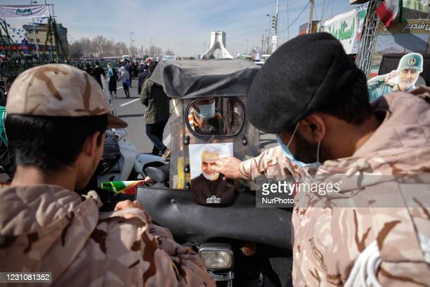 Member of the IRGC pastes a portrait of the former Iranian commander of the Islamic Revolutionary Guard Corps Quds Force, General Qasem Soleimani on...