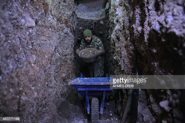 A member of the Islamist rebel group AlNusra Front fills a cart with sand as the group alledgely digs a tunnel under a military site of the Syrian...
