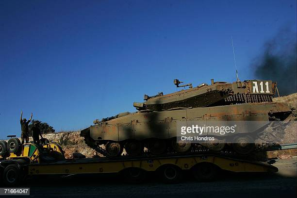 A member of the Israeli Defense Forces guides a tank onto a flatbed truck to prepare it for transport August 17 2006 near Avivim Israel The Israeli...