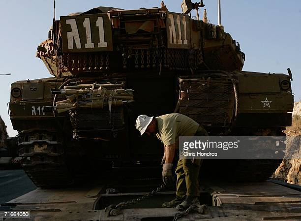 A member of the Israeli Defense Forces uses a chain to tie down a tank for transport on a flatbed truck August 17 2006 near Avivim Israel The Israeli...