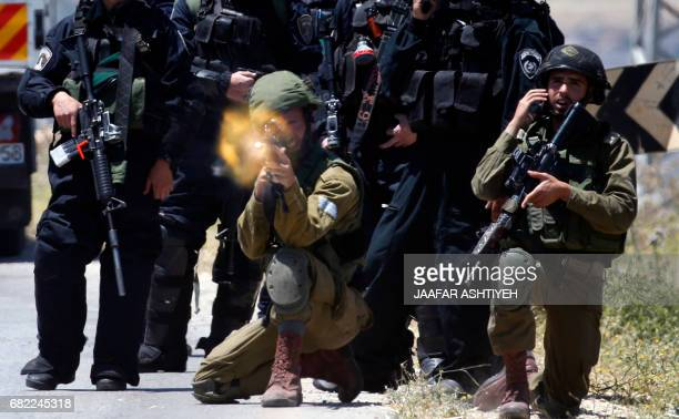 TOPSHOT A member of the Israeli forces opens fire during clashes with Palestinian protesters in the West Bank village of Beit Furik east of Nablus on...