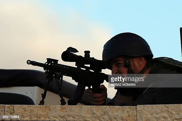 A member of the Israeli security forces aims during clashes with Palestinian demonstrators in the alJalazun Palestinian refugee camp near the...