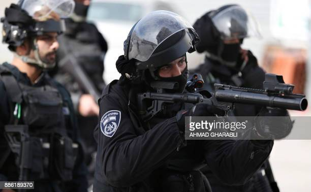 Member of the Israeli security forces aims his tear-gas launcher while patrolling a street in the East Jerusalem refugee camp of Shuafat, where a...