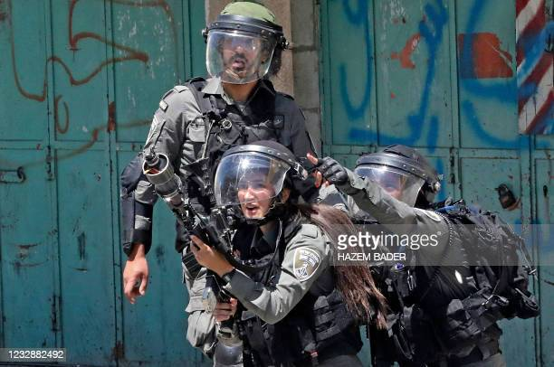 Member of the Israeli security forces fires tear gas at Palestinian protesters, during confrontations with them in the occupied West Bank city of...