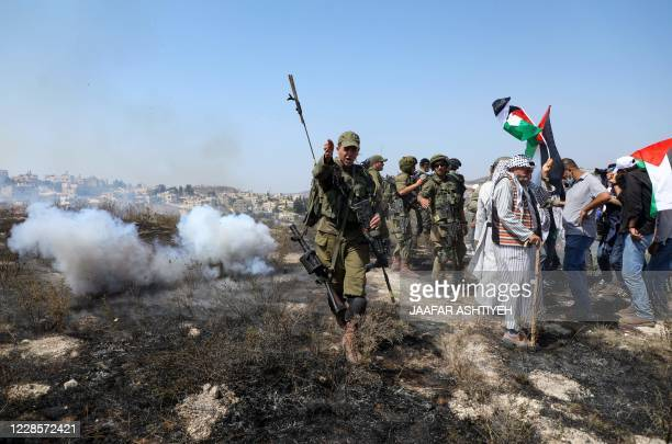 Member of the Israeli security forces gestures as Palestinians protest against Jewish settlements and the normalisation of ties with two Arab states,...