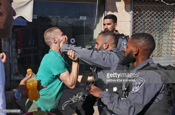 Member of the Israeli security forces pushes away a Palestinian man in the Old City of Jerusalem, on June 15 ahead of the March of the Flags which...