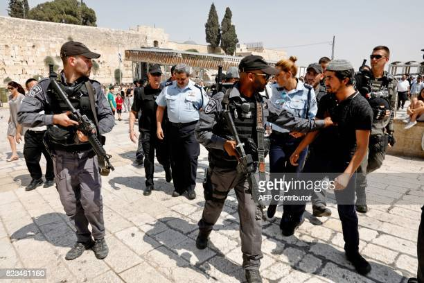 TOPSHOT A member of the Israeli security forces pushes off a rightwing activist protesting against the removal of metal detectors at the AlAqsa...