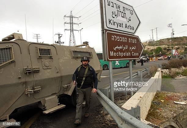 A member of the Israeli security forces walks at the scene where three Palestinians carried out two attacks a shooting and a car ramming on Israelis...