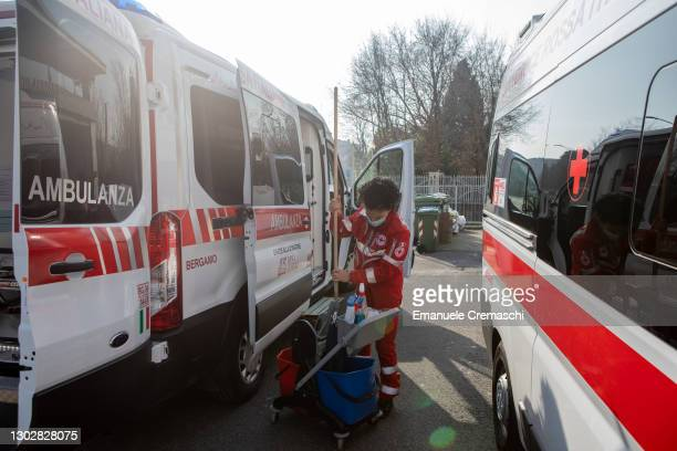 Member of the Italian Red Cross cleans an ambulance parked in front of the local Red Cross Committee on February 18, 2021 in Bergamo, Italy. The...