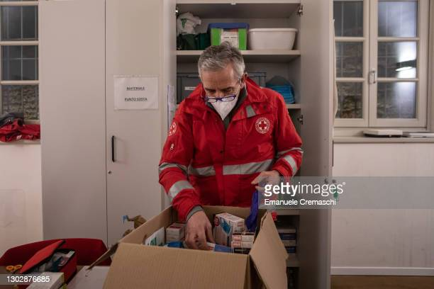 Member of the Italian Red Cross handles medicines as they volunteer inside a protected community for homeless people on February 18, 2021 in Bergamo,...