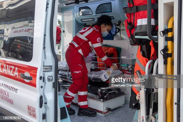 Member of the Italian Red Cross sanitizes an ambulance parked in front of the local Red Cross Committee on February 18, 2021 in Bergamo, Italy. The...