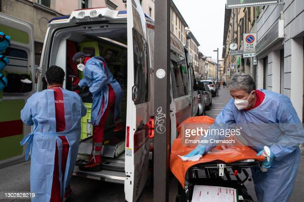 Member of the Italian Red Cross sanitizes an inflatable stretcher while two of his colleagues pack their equipment into an ambulance on February 18,...