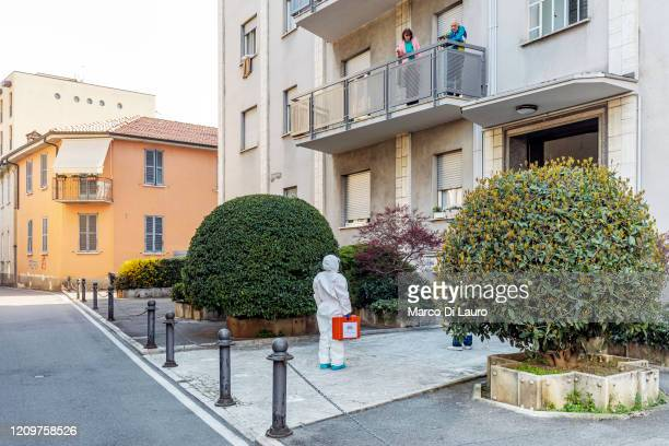 A member of the Italian Red Cross speaks with two tenants of a building during her round of home visits to COVID19 positive patients on April 3 2020...