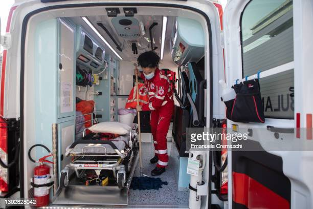 Member of the Italian Red Cross sweeps the floor of an ambulance parked in front of the local Red Cross Committee on February 18, 2021 in Bergamo,...