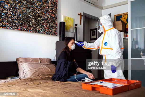 Member of the Italian Red Cross visits a patient during her round of home visits to COVID-19 positive patients on April 6, 2020 in Bergamo, Italy....