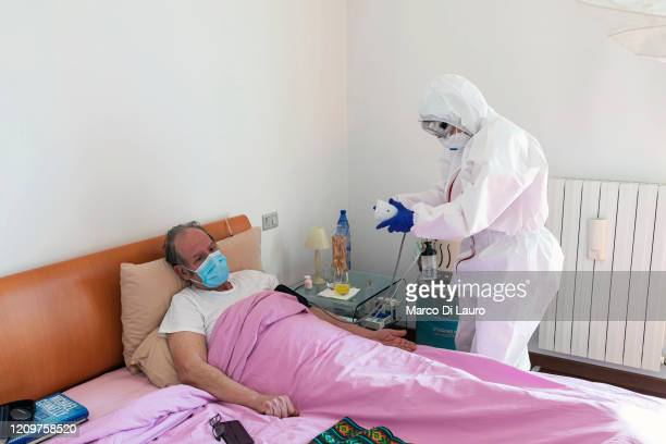 A member of the Italian Red Cross visits a patient during her round of home visits to COVID19 positive patients on April 3 2020 in Bergamo Italy The...