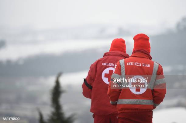 Member of the Italian Red Cross walk near the rescue operations center in Penne some 20 km from the site of an avalanche that engulfed the Hotel...