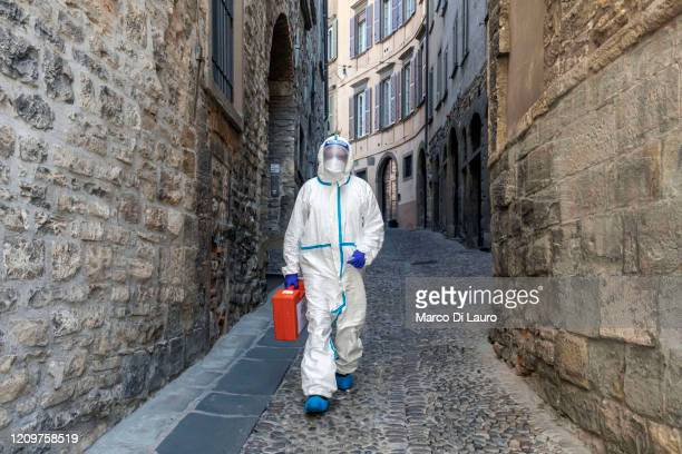 Member of the Italian Red Cross walks through an alley in the old town during his home visit to COVID-19 positive patients on April 3, 2020 in...