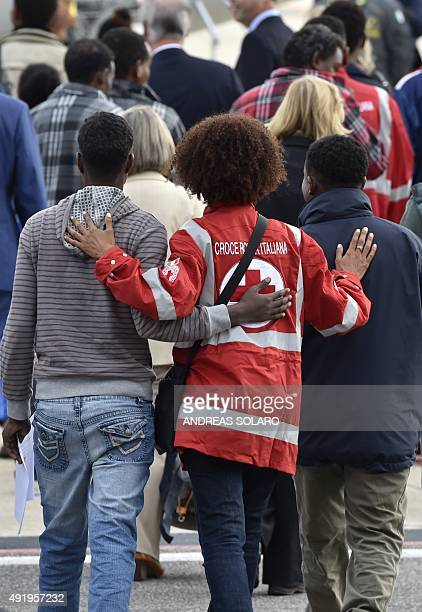 A member of the Italian Red Cross walks with a group of Eritrean refugees before they board a plane to travel to Sweden as part of a new programme of...