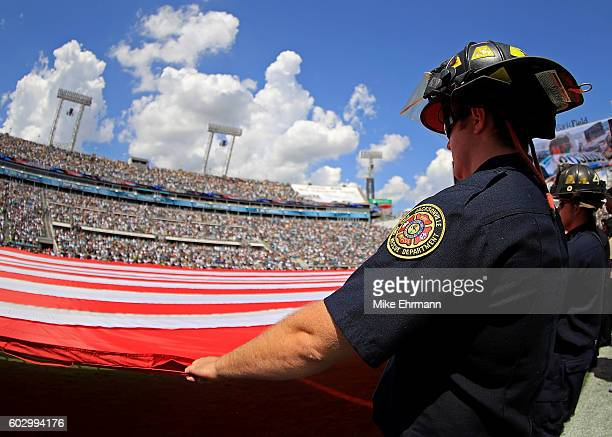 A member of the Jacksonville fire department hold the flag during a game between the Jacksonville Jaguars and the Green Bay Packers at EverBank Field...