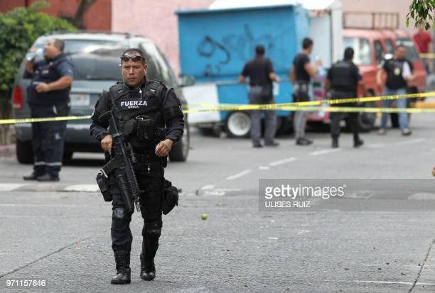 A member of the Jalisco State police is seen at the place where three people were killed during an operation in Guadalajara Mexico on June 10 2018...