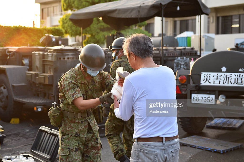 A member of the Japan Self-Defense Forces hands rice balls to people at the soup-run operated at the evacuation center a day after the 2016 Kumamoto Earthquake at the Mashiki Town Hall on April 15, 2016 in Mashiki, Kumamoto, Japan. As of April 15 morning, at least nine people died in the powerful earthquake with a preliminary magnitude of 6.4 that struck Kumamoto Prefecture on April 14, 2016.