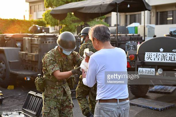 A member of the Japan SelfDefense Forces hands rice balls to people at the souprun operated at the evacuation center a day after the 2016 Kumamoto...