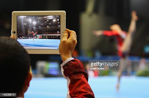 A member of the Japanese coaching staff videos a floor routine on an iPad during the women's gymnastics senior international teams competition on day...